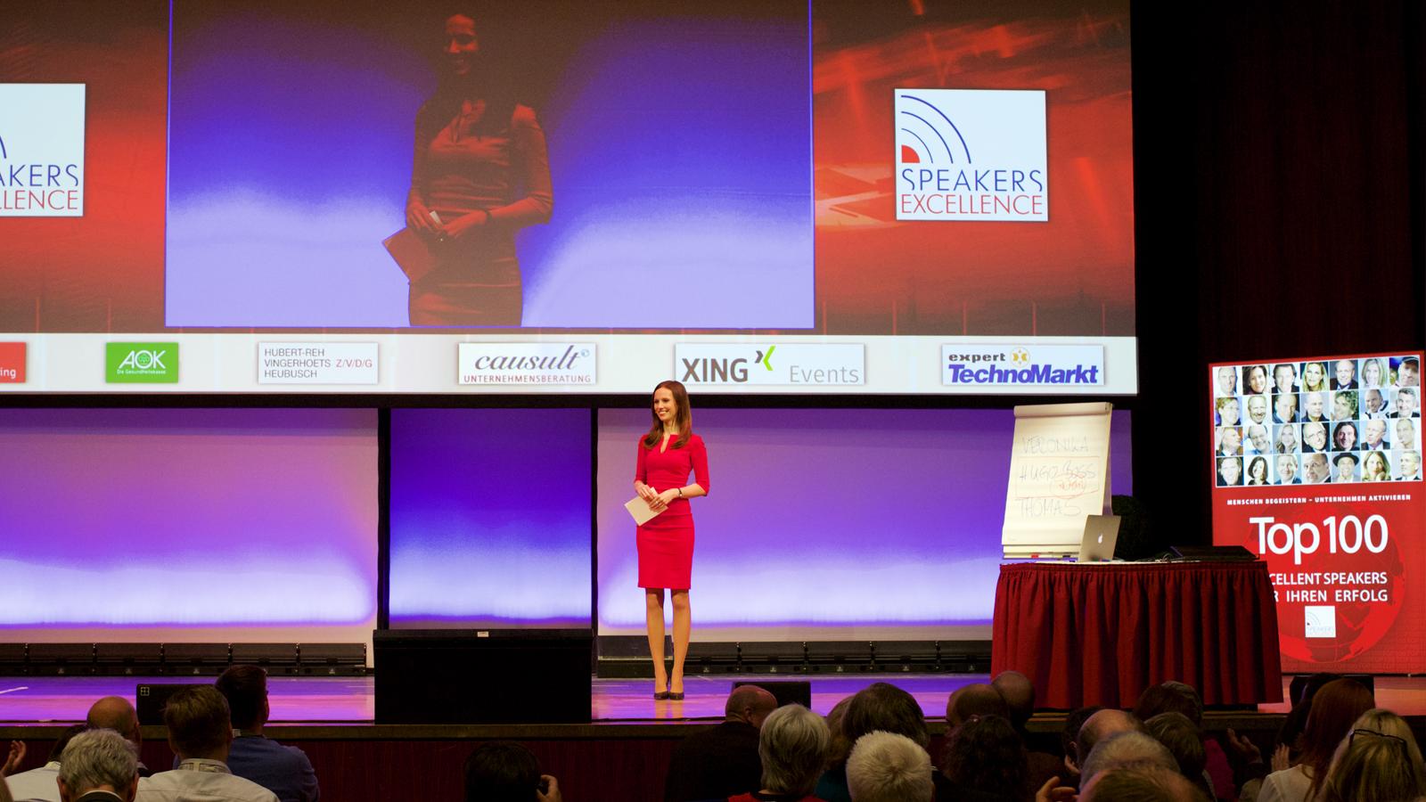 Moderatorin auf Bühne rotes Kleid