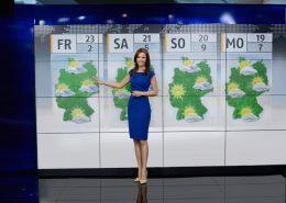 Moderatorin aus Berlin vor Wetterkarte